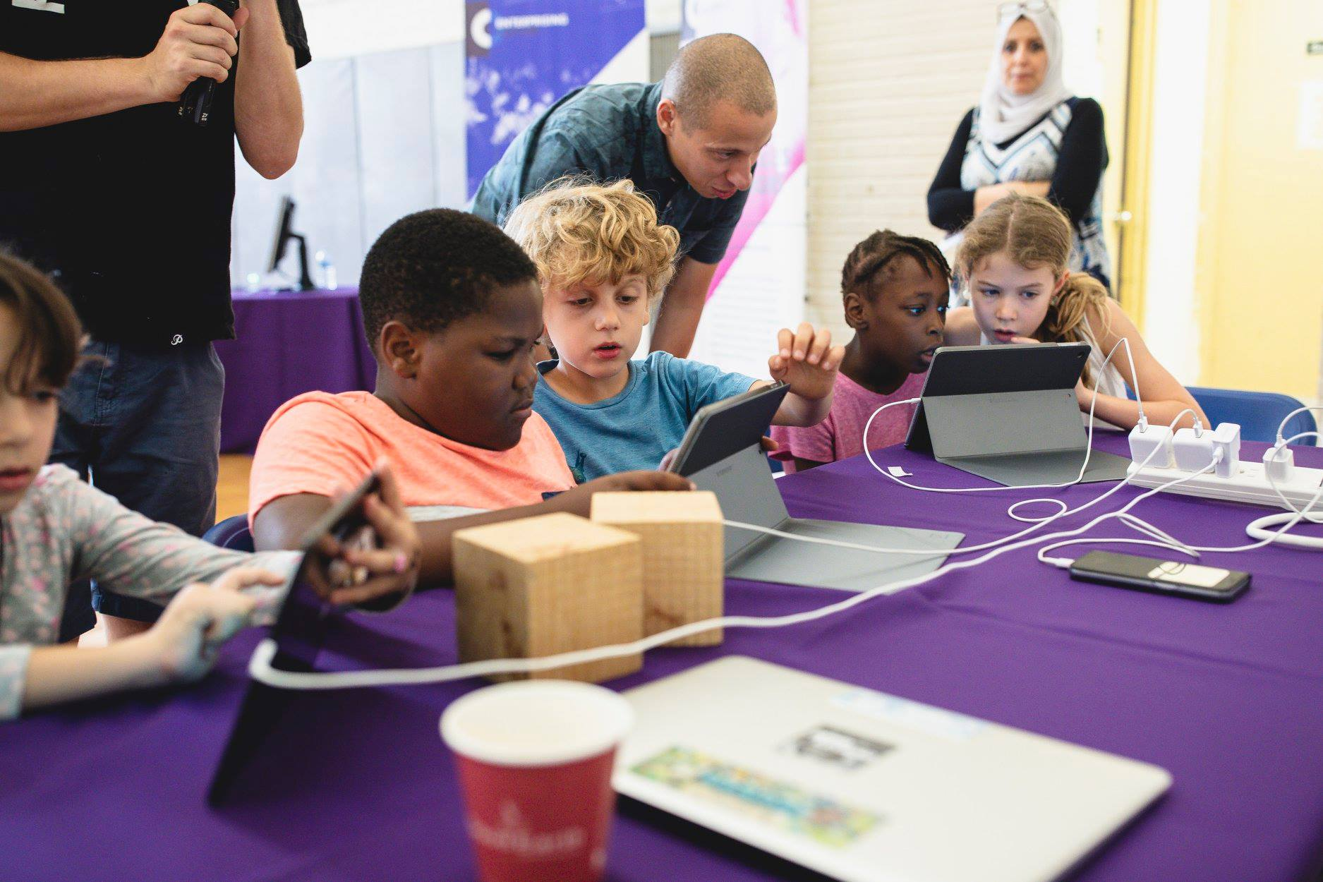Two pairs of children sit at a purple table. Each pair is looking at a tablet in front of them. A man stands between the groups.