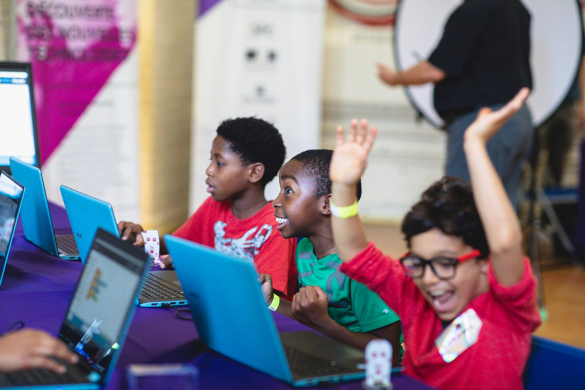 Three children sit at a table with laptops in front of them. The child sitting in the middle is smiling widely and the boy next to him is cheering with his arms in the air.