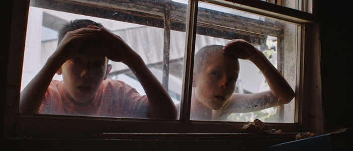 Two children look through a window into a building