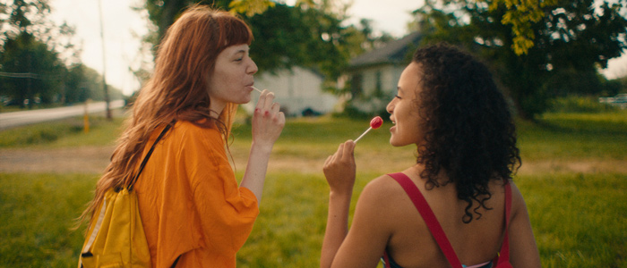 Two girls look at each other while one eats a lollipop