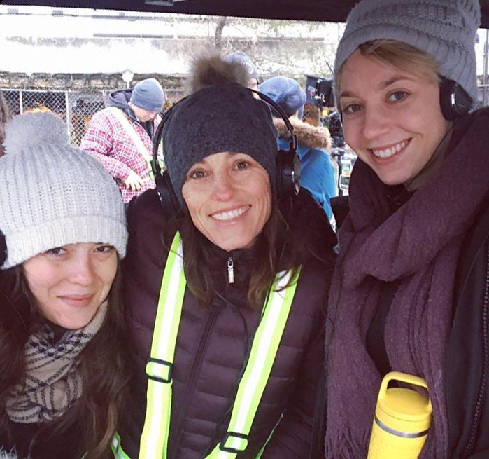 Three women dressed in winter wear on a movie set.