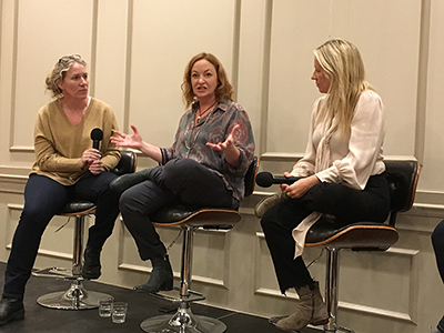 Three women sitting on a stage, engaged in a panel discussion.