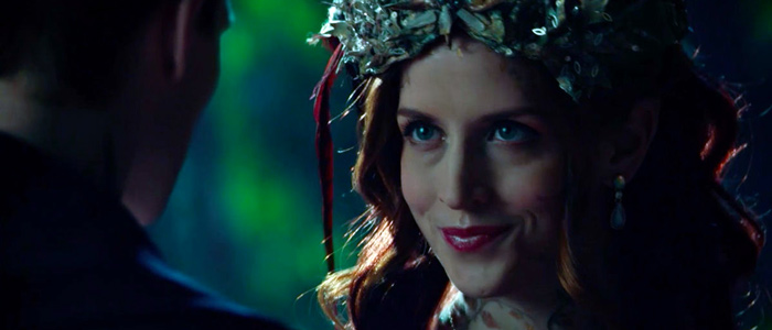 Red-haired woman wearing leafy crown looks at a man