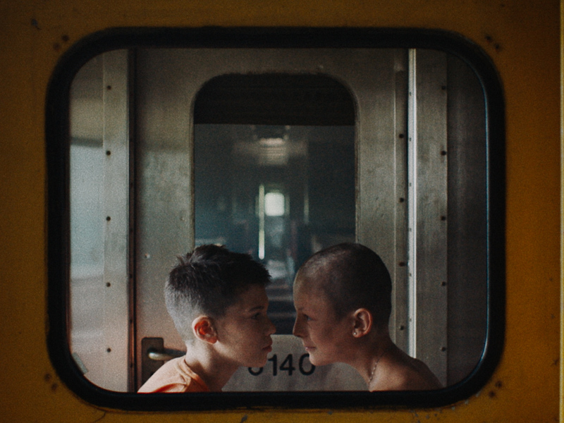 Two boys face each other against a dirty industrial set of doors and windows.