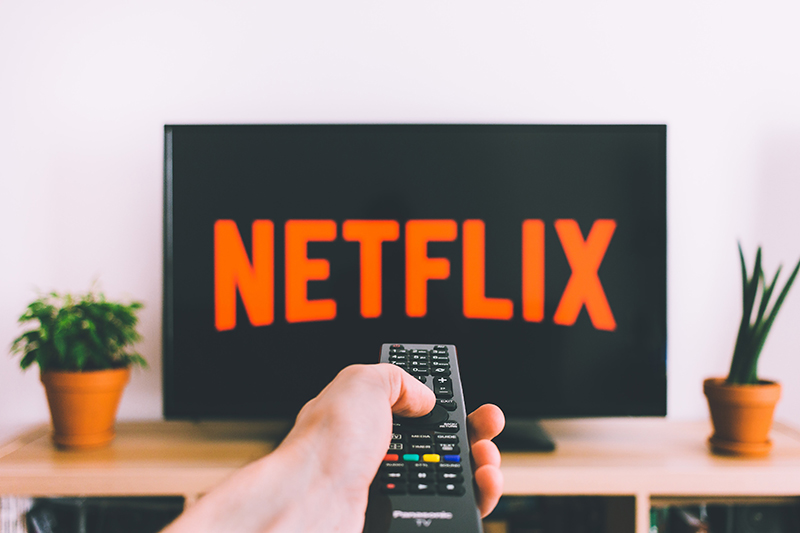 A television with the 'Netflix' logo on it. In front of the TV is a hand holding a remote.