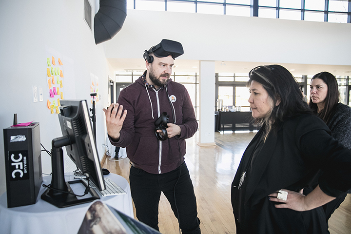 A man with a VR headset around his head is talking to two women as they stand next to him and look at a computer screen.