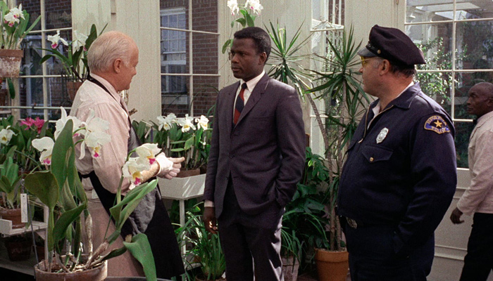 Two detective speak with a man in a greenhouse