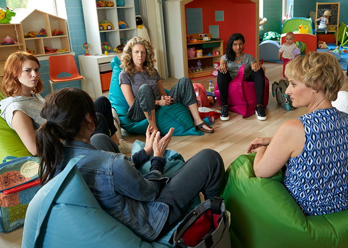 A group of women sit on beanbag chairs in a circle
