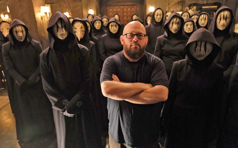 A still photo from a TV show of a man standing in glasses, surrounded by a crowd of people in masks.