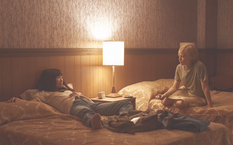 Two females sitting in a hotel room on opposite beds, the female on the left is laying down against the headboard, and the female on the right is wearing a t shirt sitting up on the bed.