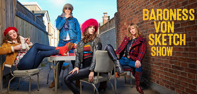 Four women wit in an alley, wearing fancy winter clothes.