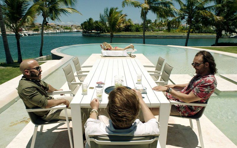 A still image of three men sitting at a poolside table talking to each other over some drinks, and a lady laying on her back on the tanning chair by the pool in a distance.