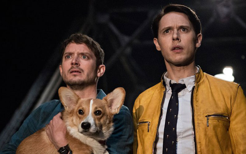 Two men who are standing side by side each other, the man on the left is holding a corgi dog, and both of them have shocked expressions on their faces.