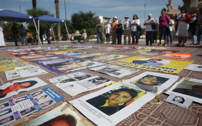 A still shot of the ground covered in pictures of people, with people surrounding them and looking at them.