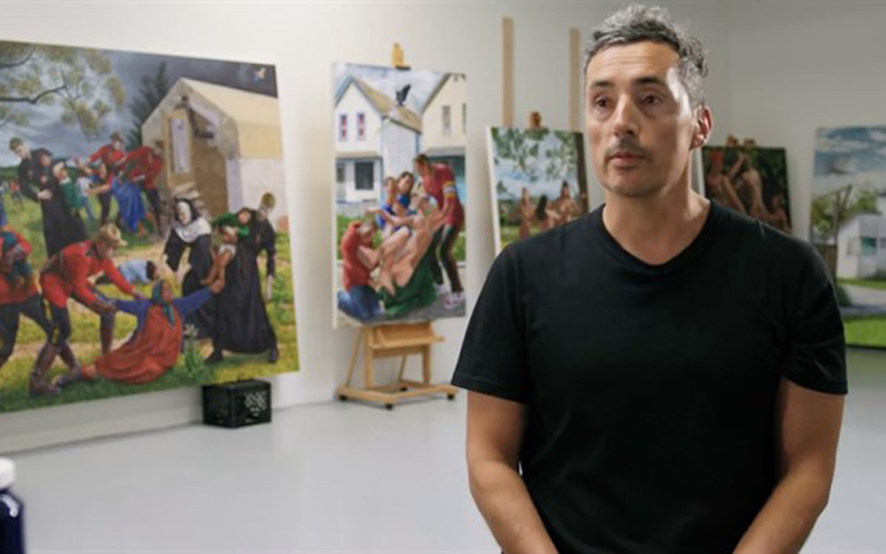 A still image of a man standing in front of a gallery talking to the camera