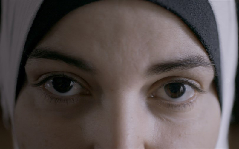 A close of a girls face, focusing on her eyes while she wears a religious head cover