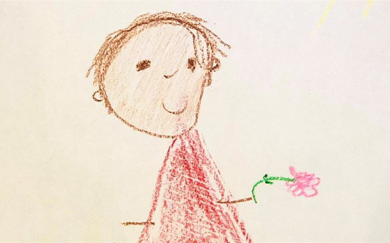An image of artwork that was drawn by a young child which features a drawn boy holding a flower.