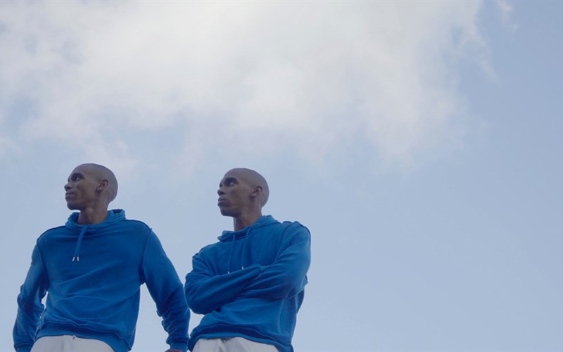 A image of two males that are twins, standing by each other wearing the same blue sweater, with the clear sky in the background.