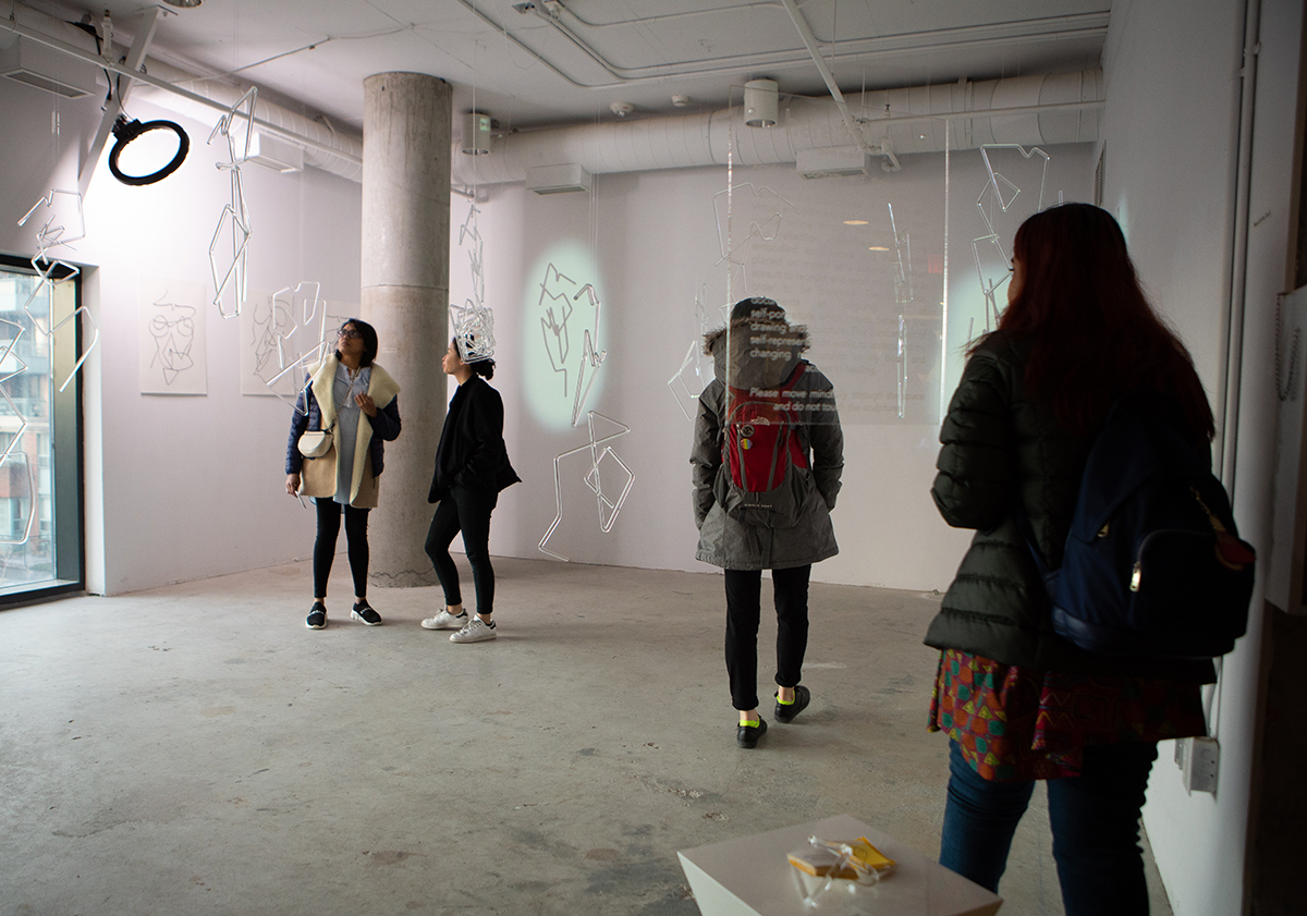 Four people standing in a white room with plexiglass tube structures hanging from the ceiling.
