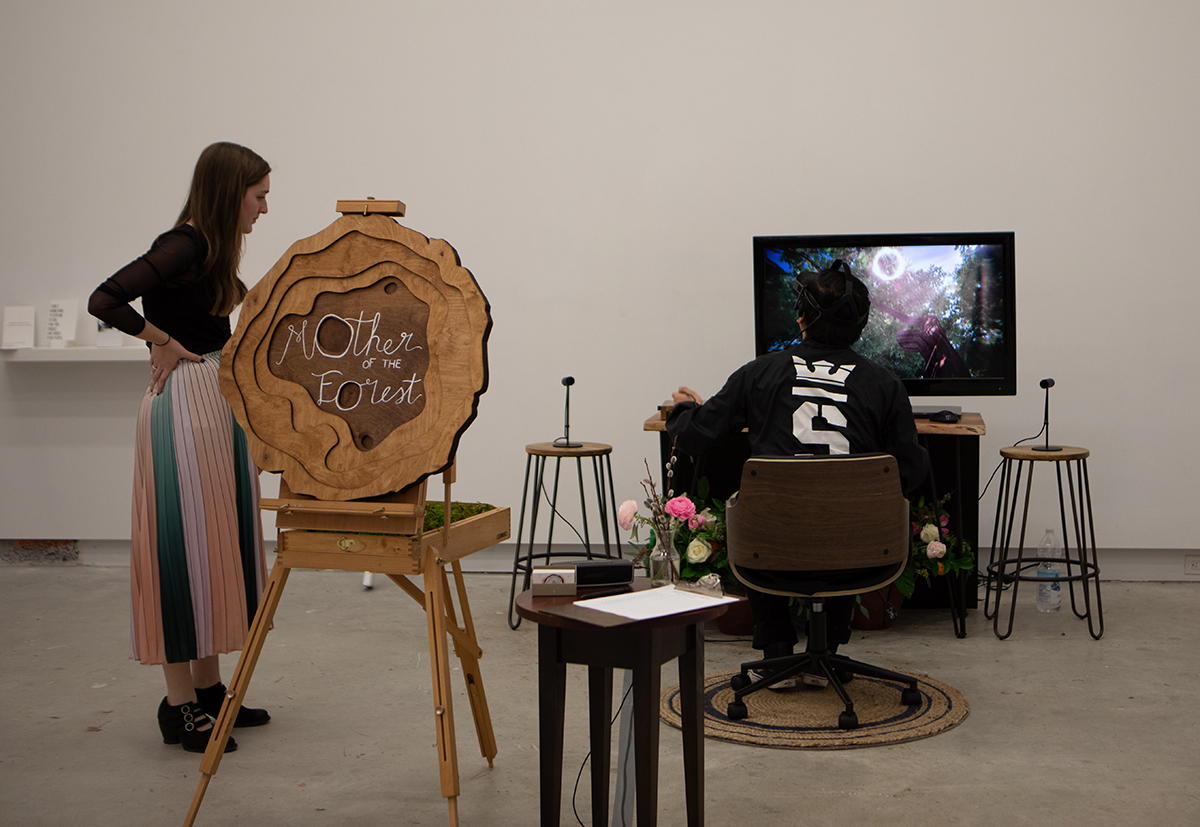 A man sitting in front of a TV screen wearing a VR headset. Next to the man is a woman and a wooden sign that reads 'Mother of the Forest'.