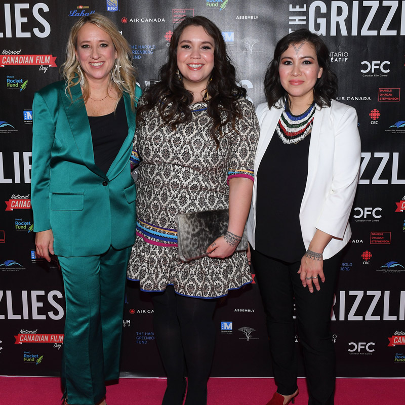 An image of three ladies standing side by side on the red carpet, taking a photo together.
