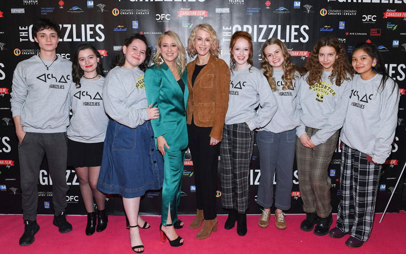 Two females that are surrounded by young teens that are al wearing the same grey sweater, taking a photo on the red carpet together.