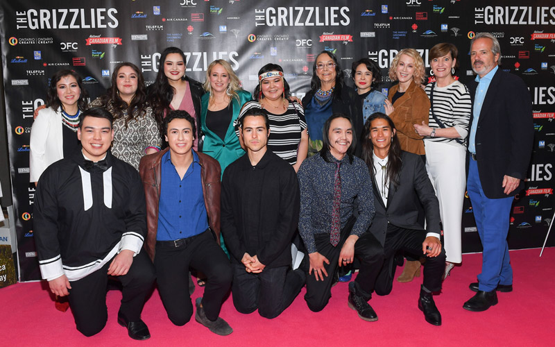 A group photo of a cast and crew on a red carpet.