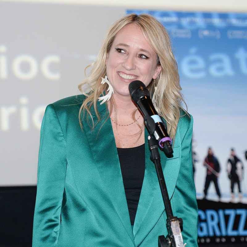 A blonde female in a green silk suit talking into the microphone on stage.