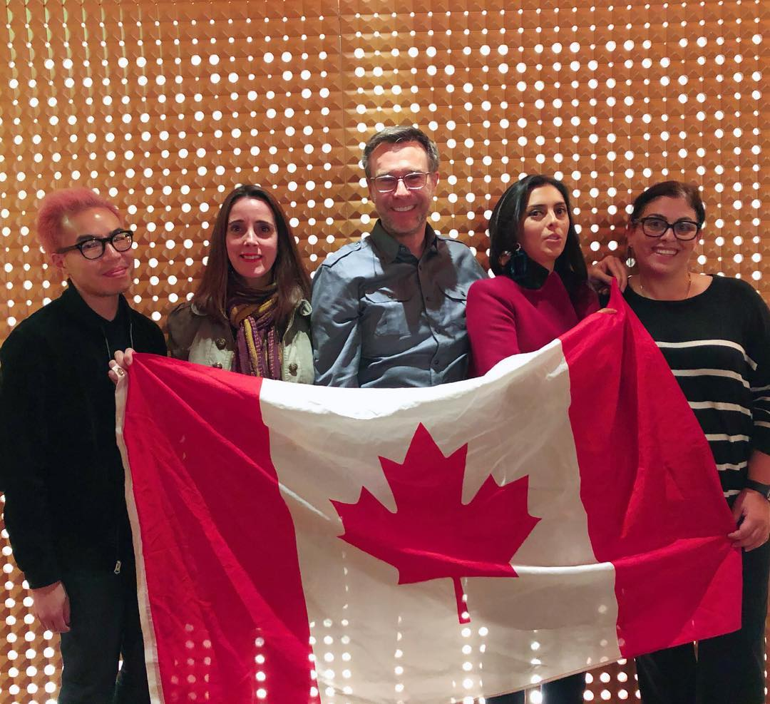 Five people holding up a Canadian flag.