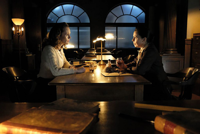 Two women sit at a table at night.