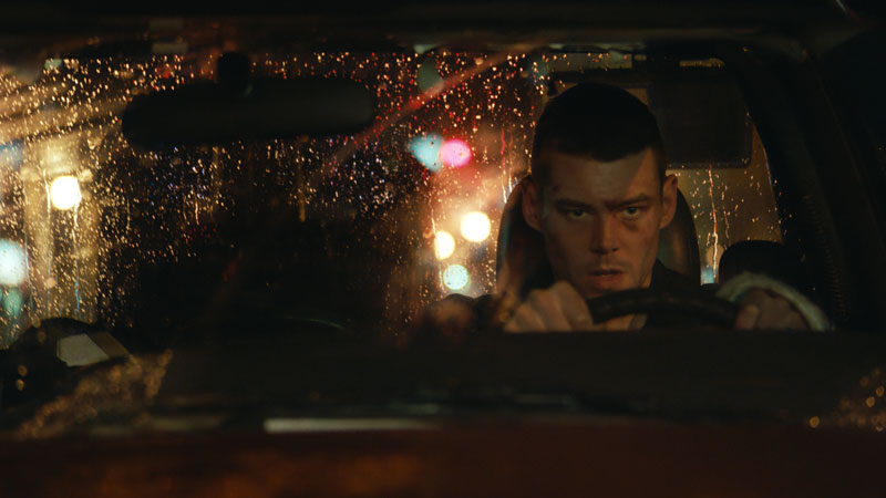 A man drives at night, the reflective glare of traffic lights on his windshield.