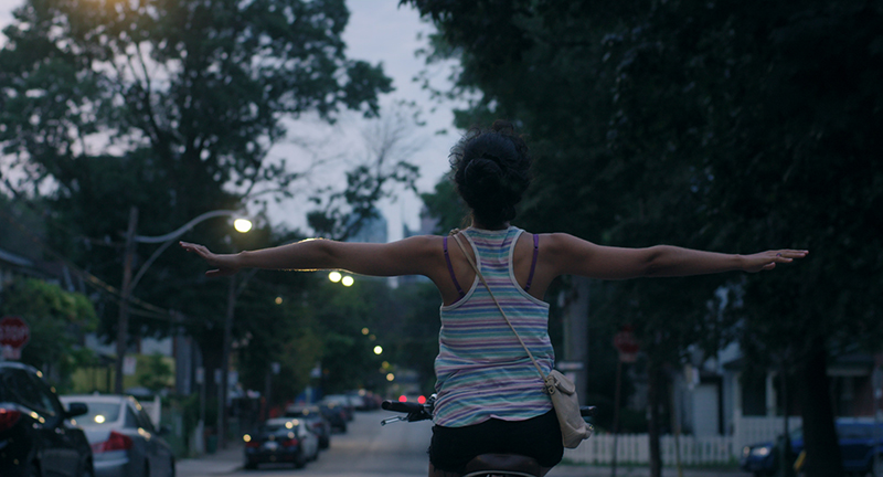 A woman seen from behind rising a bicycle, arms outstretched to the side.