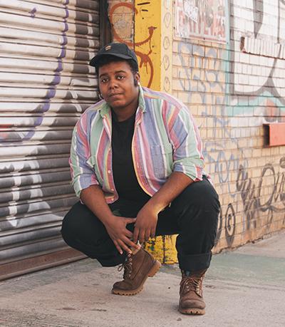 A transgender man crouched beside a graffiti-tagged wall.