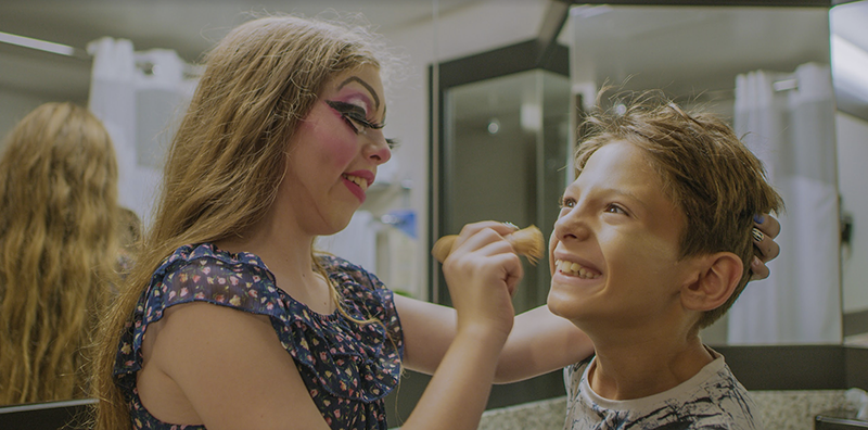 Two children help each other prepare for a performance by applying makeup.