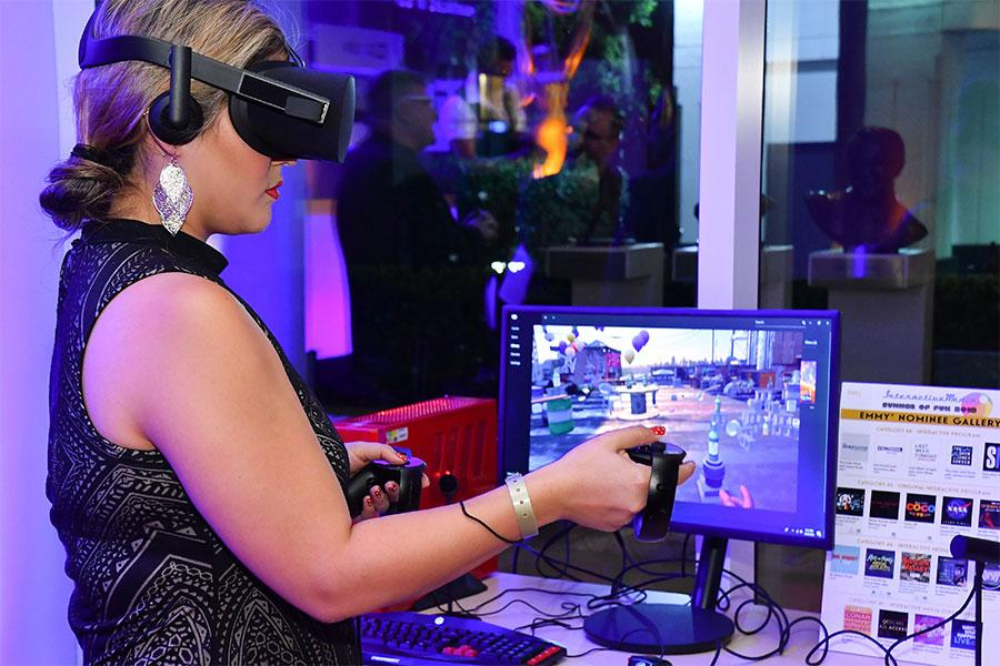 A woman wearing a VR headset and holding a controller while standing in front of a computer monitor.