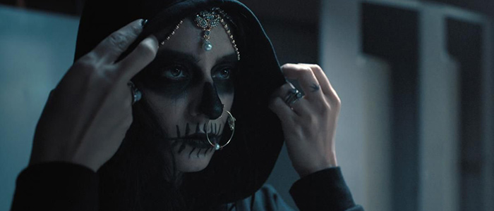 Woman with skull makeup on her face pulls up a black hood around her head