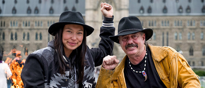 Two Indigenous folks stand together while holding up their fists in solidarity