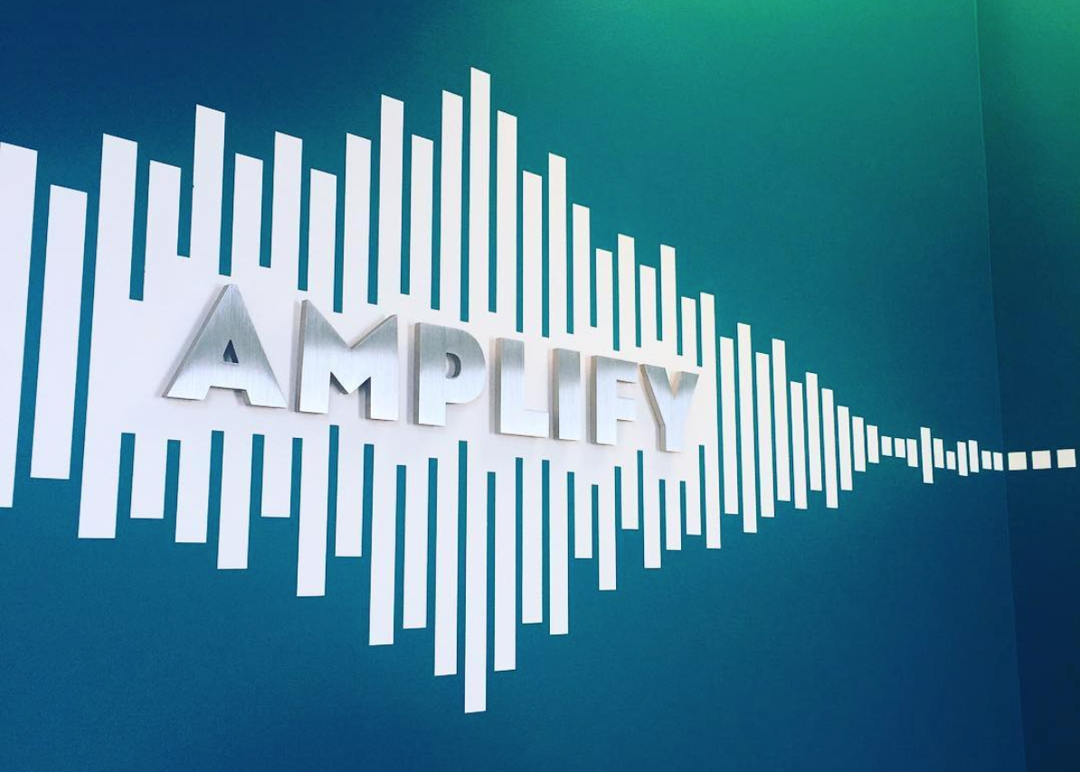 Blue and white wall with 'Amplify' in metal letters.