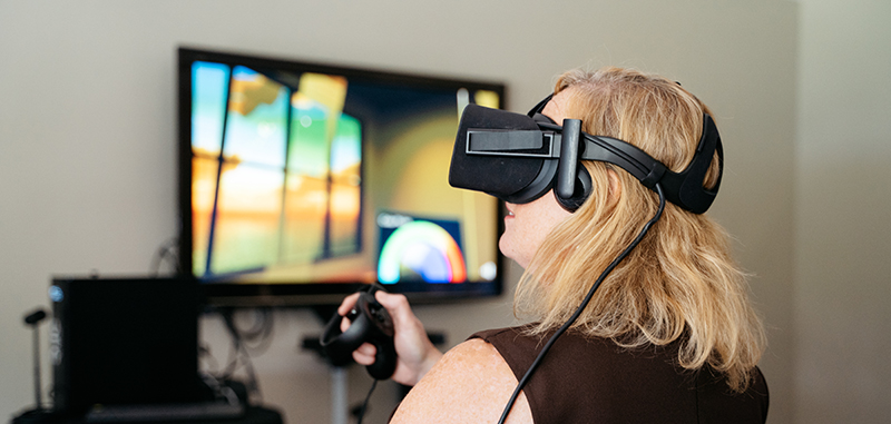 A woman in a VR headset, with a TV screen blurred out in the background.