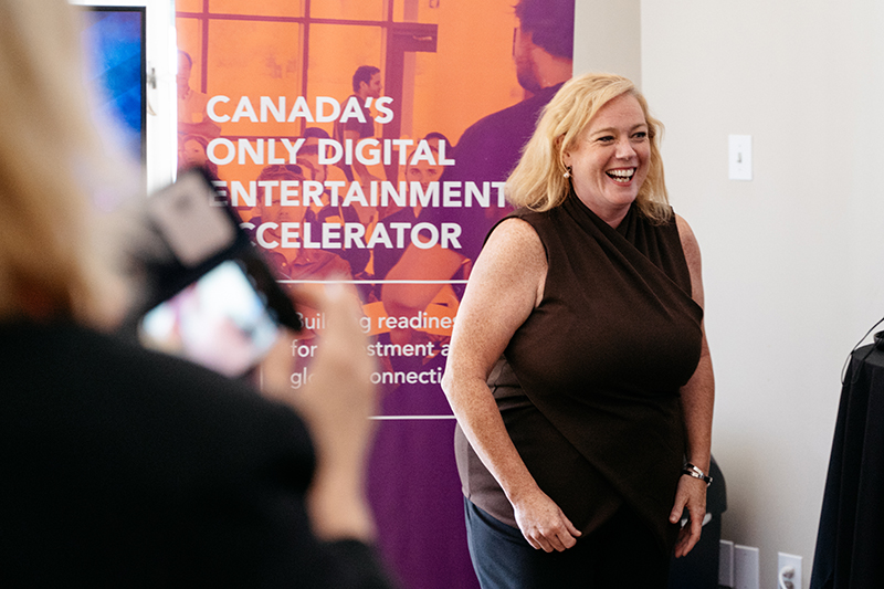 "A woman smiling, standing in front of a banner that has the words ""Canada's Only Digital Entertainment Accelerator."""