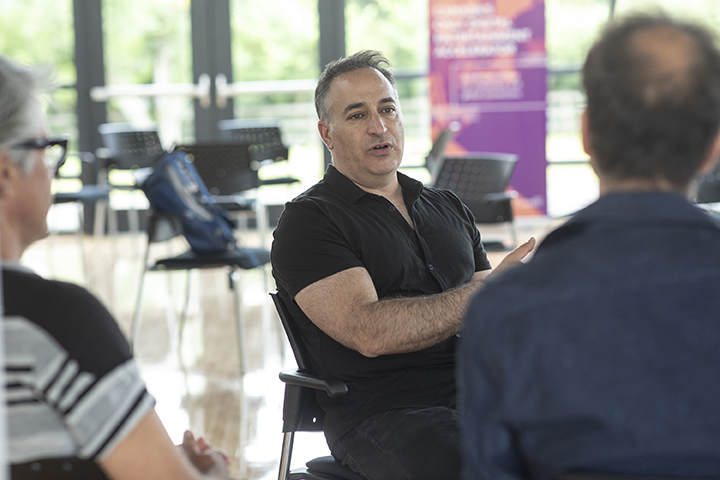A man in black shirt sitting and talking to two other people.