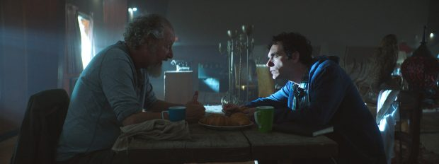 Two men sit across a table from one another in a dark room