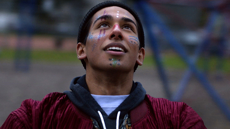 A young man with glittery paint on his face, looks up towards the sky