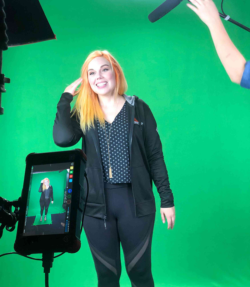 A woman being interviewed in front of a green screen.