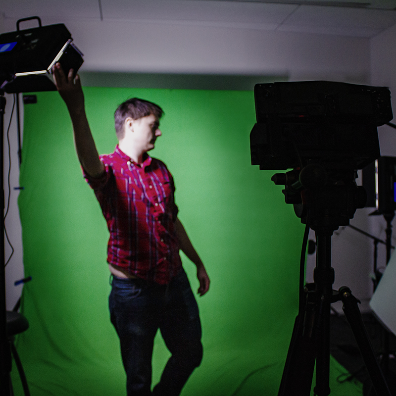 A man setting up stereoscopic-volumetric capture technology in front of a green screen.