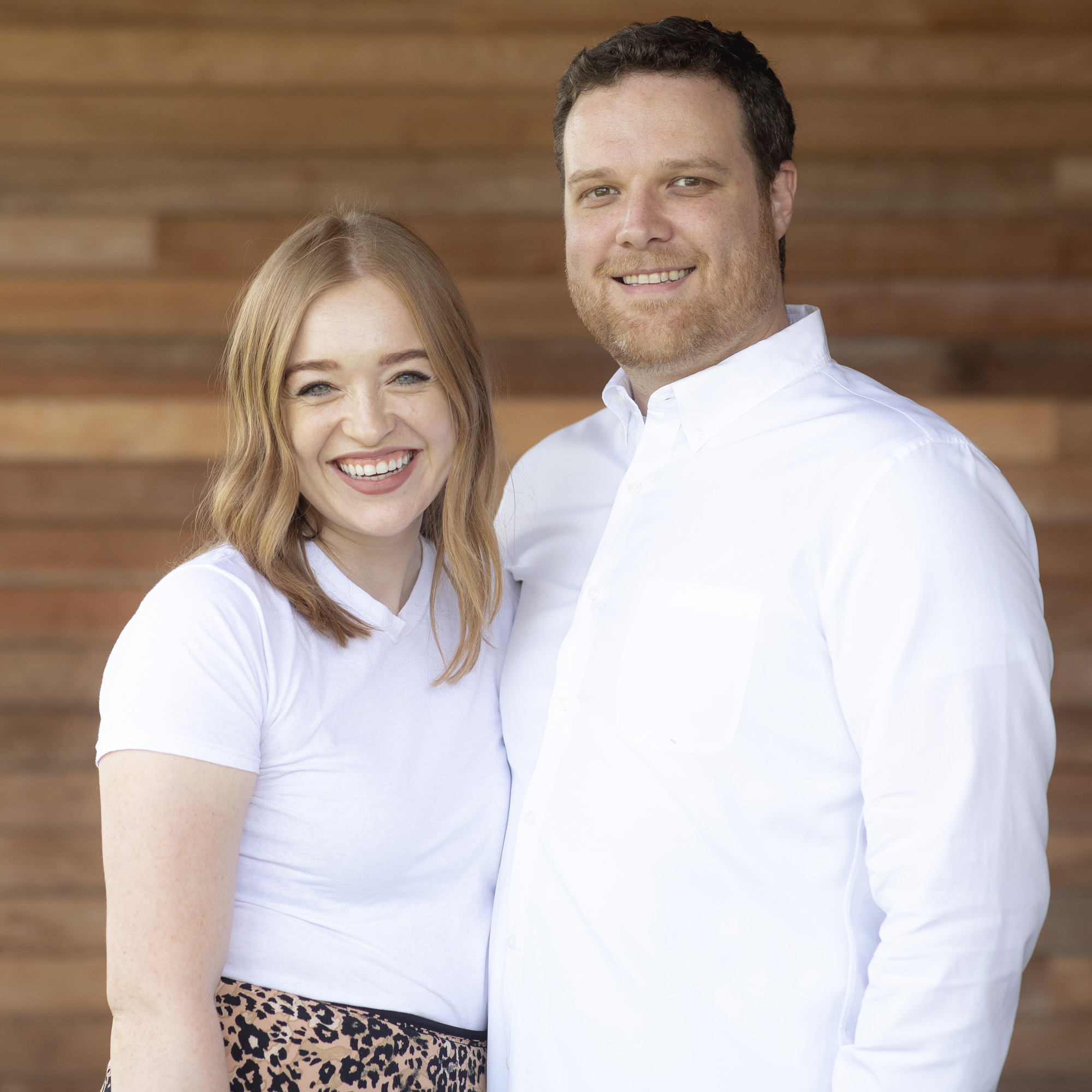 A man and a woman stand side-by-side posing for a picture wearing white shirts