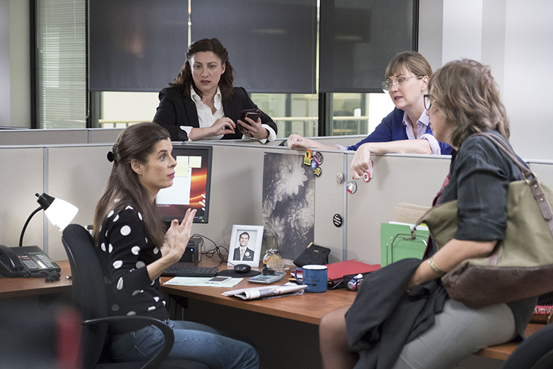 Four women stand around cubicles in an office talking