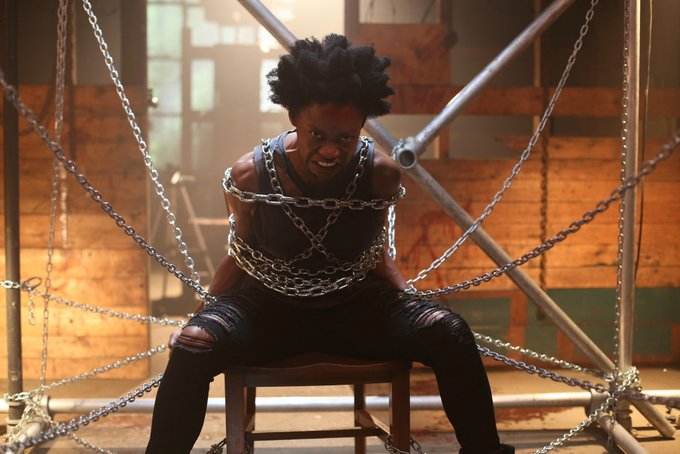 A woman with an angry look on her face is tied to a chair using metal chains