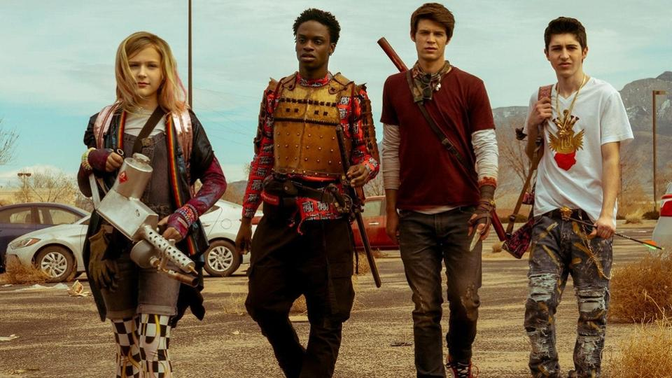 Four teenagers walking side-by-side holding various weapons