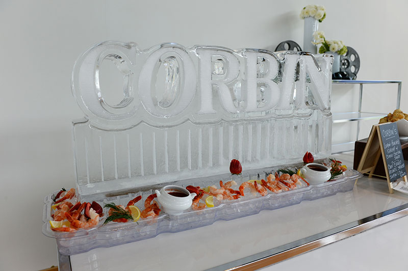 An ice sculpture and cocktail shrimp display at an event